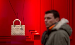 a man passes a red window with a white Dior on show