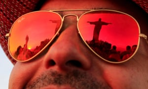 The statue of Christ the Redeemer is reflected in the sunglasses of a tourist in Rio de Janeiro.
