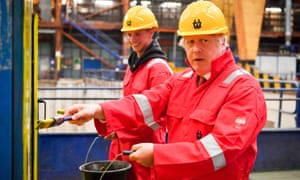 Boris Johnson helps paint machinery during a visit to Devon on Tuesday. The prime minister said the government may change guidance on face masks in schools.