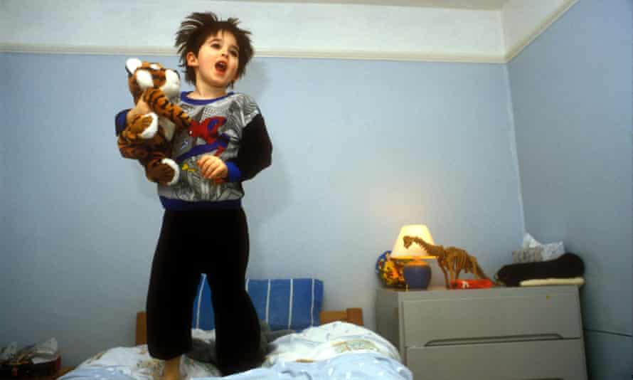 Young child jumping on bed