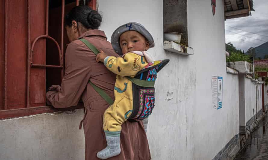 wanita dengan anak diikat ke belakang berdiri di jendela