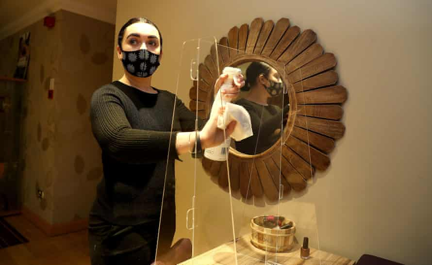 The spa treatments manager at Cottons Hotel and Spa in Knutsford, Cheshire, cleans a protective screen before its reopening after the end of the second English lockdown