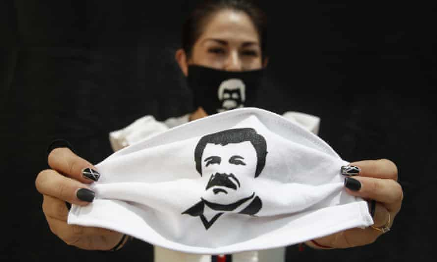 A person holds a face mask, which depicts Joaquín 'El Chapo' Guzmán, in Guadalajara, Mexico. Jesús 'El Rey' Zambada gave evidence against the drug lord at his trial in New York.