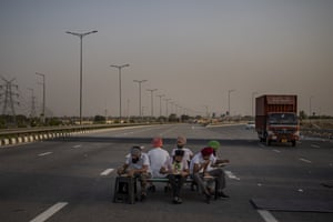 Farmers eat a meal during a 24-hour blockade of a major expressway as part of their ongoing protests against new farm laws in Dasna