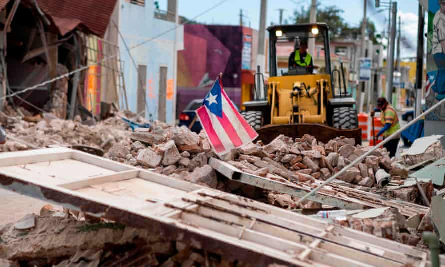 A Puerto Rican flag waves on top of a pile of rubble in Guanica.