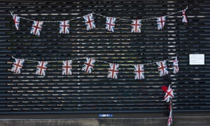 Boarded up shopfront with Union Jack bunting