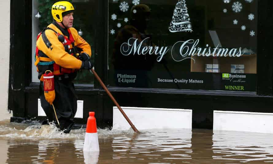 A member of the emergency services walks through flood waters past a shop in York.