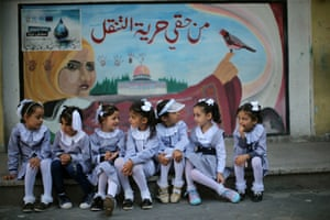 Palestinian schoolgirls sit in front of a mural on the first day of a new school year, at a United Nations-run school in Khan Younis in the southern Gaza Strip August 28, 2016