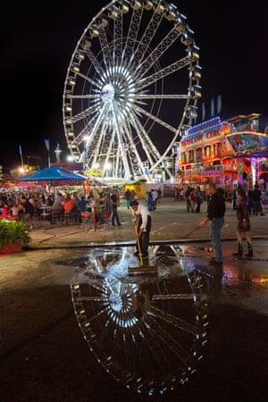 A carnival worker sweeps away water