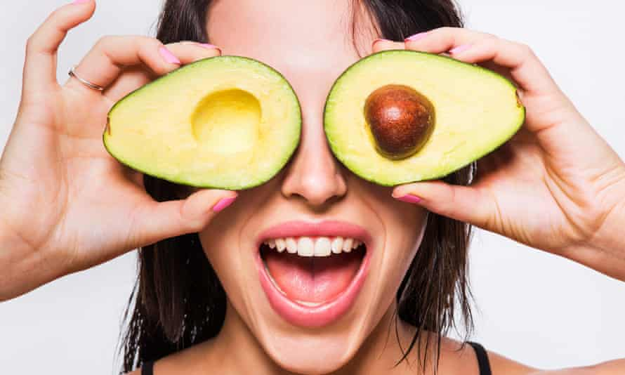 Woman holding an avocado half in front of each eye