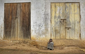 A young Ugandan boy sits outside the front of his house in the village of Kyanukuzi.