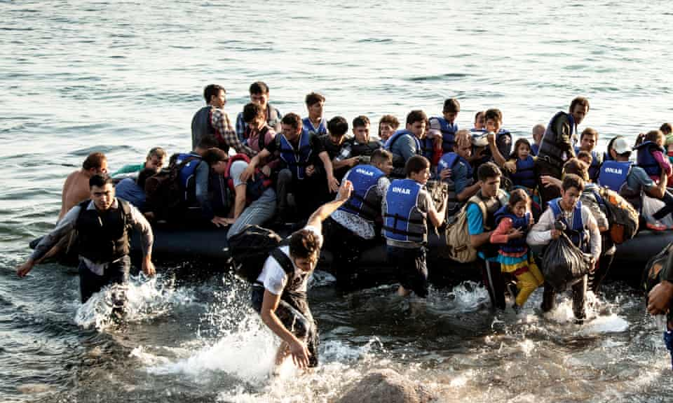 A boat dangerously overloaded with refugees lands near Molyvos on the Greek island of Lesbos, July 2015