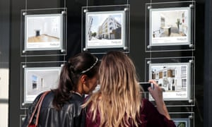 Two women look at houses for sale in an estate agent's window.