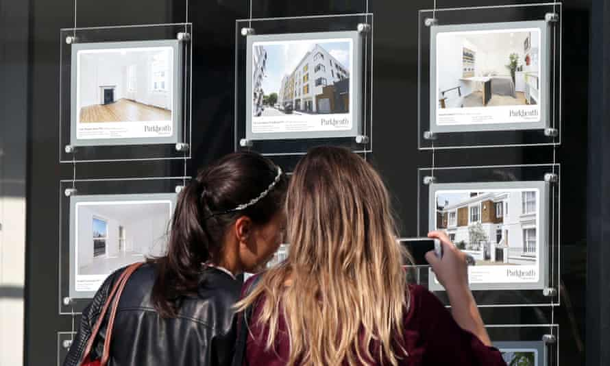 A couple of women look at an estate agent's window.