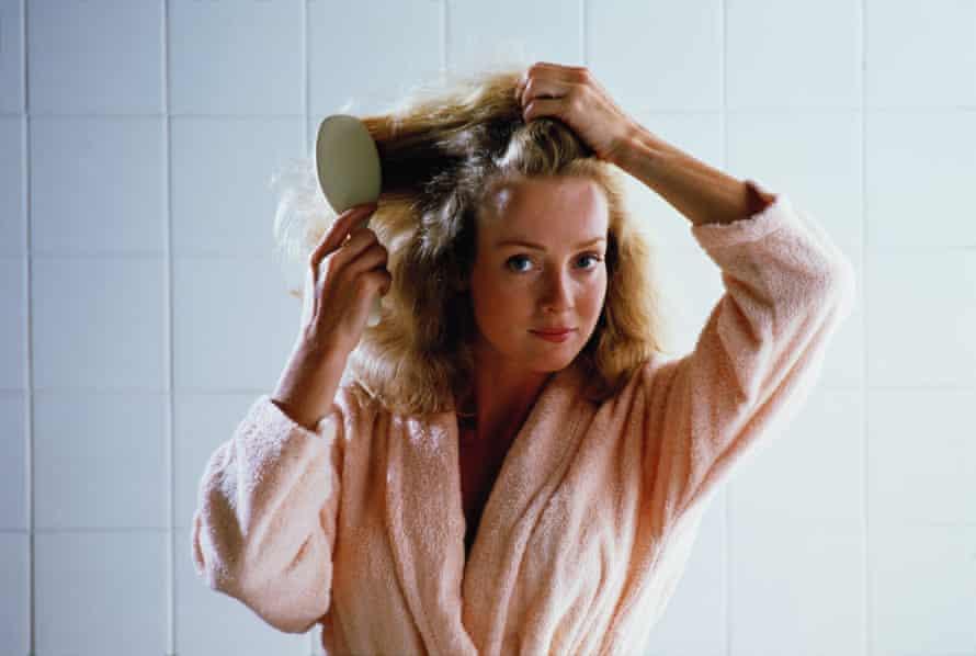 Woman in peach dressing gown brushing hair.