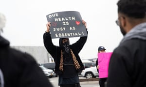Chris Smalls holds a sign at an Amazon building on 30 March. Smalls had led a workout demanding the company shut the facility after multiple workers tested positive for Covid-19.