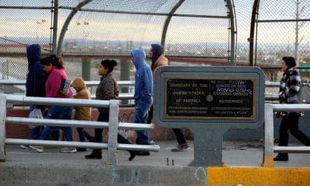 People walk on the international border bridge Paso del Norte to cross to El Paso from Juarez