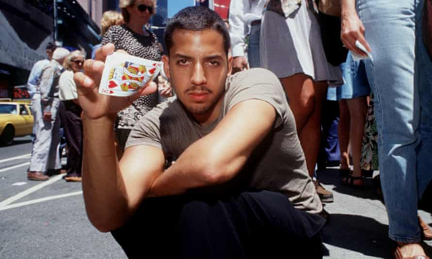 David Blaine crouching in a street and holding up playing cards.