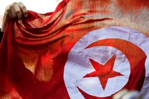 A Tunisian flag is held aloft during celebrations marking the fourth anniversary of the country's 2011 revolution