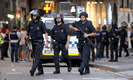 Police officers near the Las Ramblas area of Barcelona after a van ploughed into a crowd, killing at least 13 and injuring more than 80 on Thursday night.