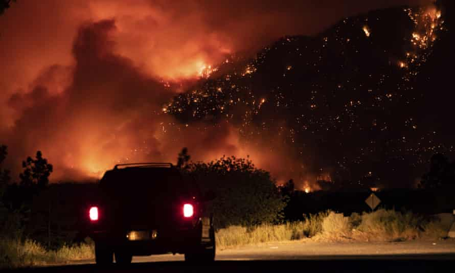 A motorist watches from a pullout on the Trans-Canada Highway as a wildfire burns on the side of a mountain in Lytton, British Columbia, on Thursday.