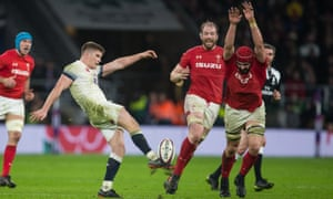 Cory Hill of Wales attempts to block a kick from England's Owen Farrell during the sides' close battle at Twickenham.