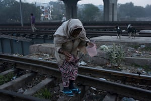 A woman looks for a place to defecate on the railroad tracks, early in the morning in the Anna Nagar slum, in Delhi