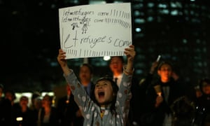 A girl holds a sign in support of refugees during a vigil in Sydney.