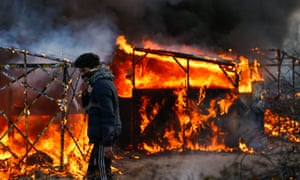 Shelters at the Calais refugee camp ablaze at the start of the clearing operation.