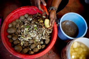 Evaline Atieno, who runs a chip and sausage shop and cafe on one of the main lanes in Kibera peels the day's batch of potatoes