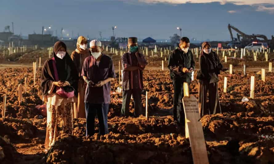 Relatives pray by the graves of Covid-19 victims during a funeral at cemetery in Jakarta