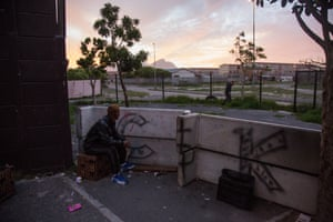 An alleged 'Clever Kids' gangster sits behind a number of upturned benches used as a shooting barricade during skirmishes with rivals across the street in Manenburg, Cape TownAll images by Shaun Swingler. Watch the pilot Ridealong video on the Daily Maverick Chronicle here