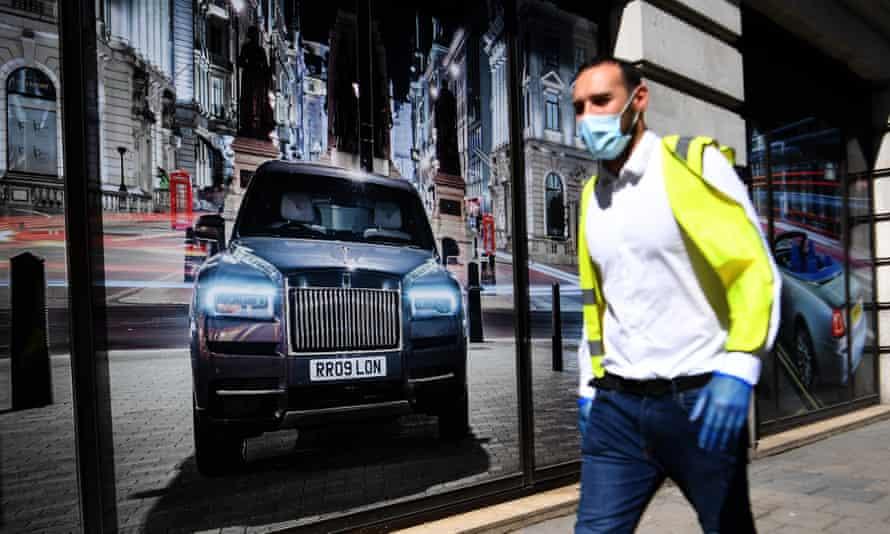 A pedestrian passes a Rolls-Royce showroom in London