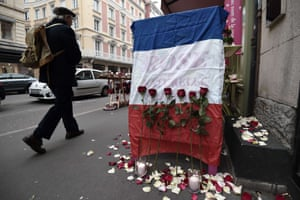 A man walks past a French national flag put outside a flower shop in Strasbourg, eastern France