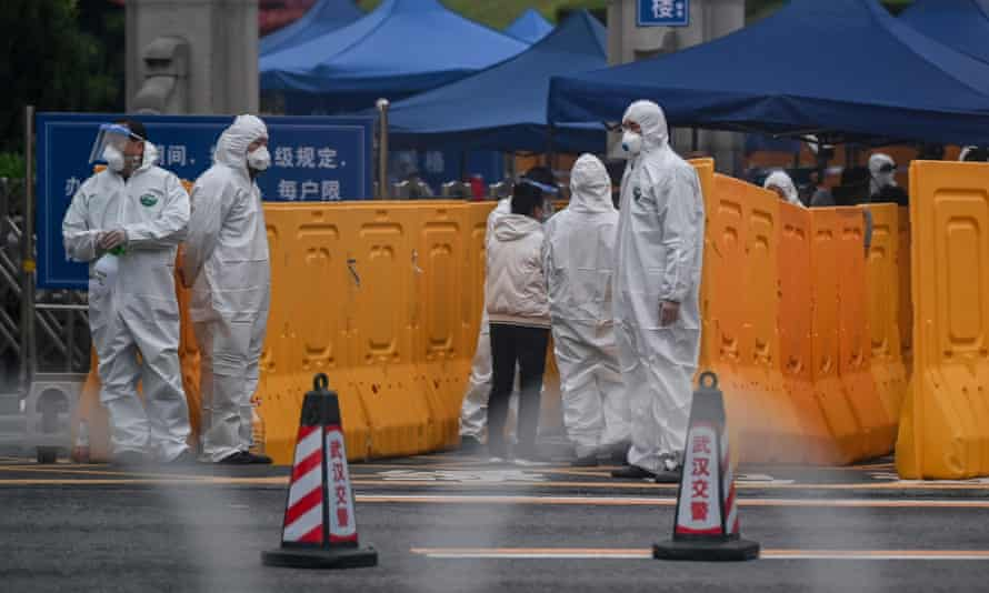 People wearing protective suits control an access point to the Biandanshan cemetery in Wuhan.