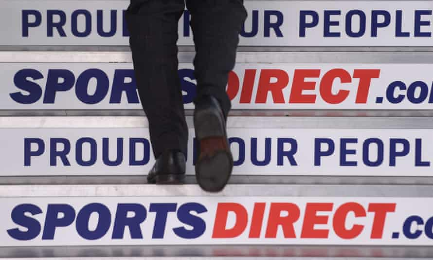 A man walks up airline steps with Sports Direct advertising