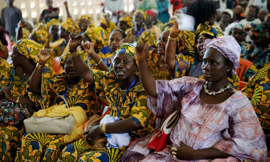 """Women chant """"down with Ebola"""" before the inauguration of an Ebola treatment center in Macenta in November 2014."""