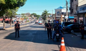 """Paraguayan police officers control cars at a check point during the """"preventative and compulsory"""" lockdown of the population decreed by Paraguayan President Abdo Benitez due to the pandemic outbreak of the new Coronavirus, COVID-19, in Asuncion, on March 23, 2020."""