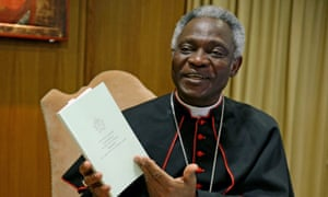 Cardinal Peter Turkson with a copy of Pope Francis's encyclical.