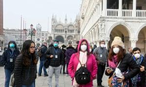 Tourists wearing protective masks visit Venice.