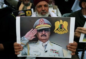A Libyan man carries a picture of Khalifa Haftar during a rally in Benghazi