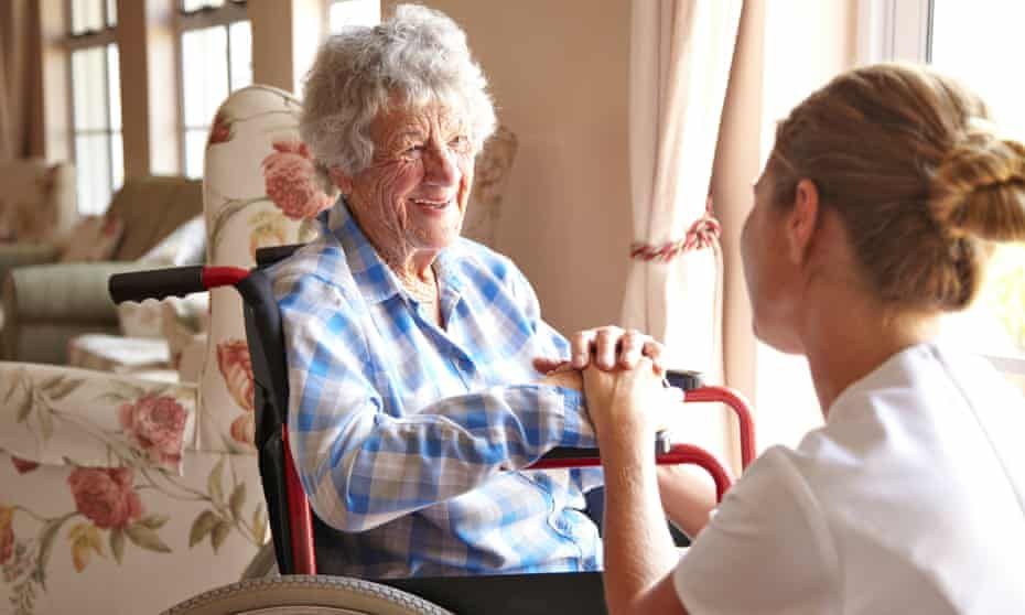 Care worker holds hand of older woman in wheelchair