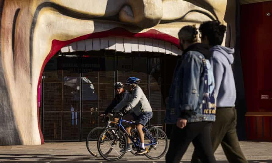 People walk and ride bikes past Luna Park in St Kilda
