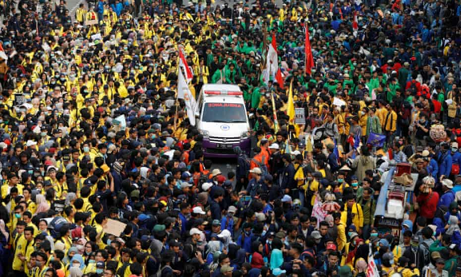 Protesters allow an ambulance to pass through in Jakarta