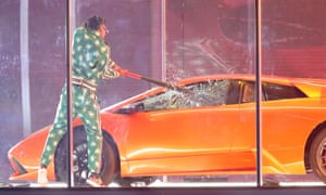 An assistant smashes the windows of a sports car as US singer-songwriter and rapper Kendrick Lamar performs