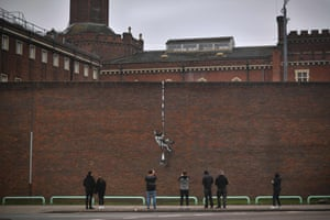 Reading, England. Members of the public look at street art on the side of Reading prison. The picture shows a prisoner, possibly resembling the famous inmate Oscar Wilde, escaping on a rope made of bedsheets tied to a typewriter