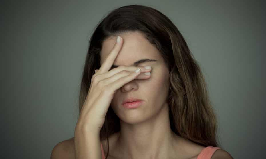 A woman with her hand over her eyes looking stressed.