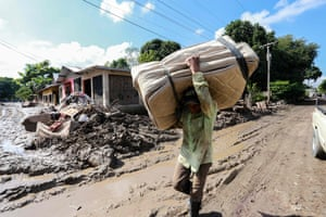 A victim of tropical storms carries a mattress along a street covered in mud in Cortés, Honduras