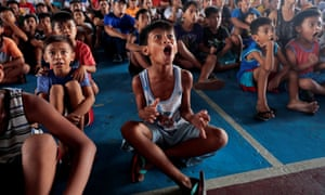 Young Filipino boxing fans watch Manny Pacquiao on TV in Marikina, the Philippines