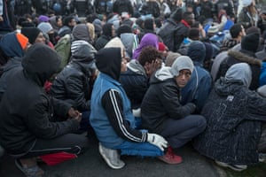 Refugees sit on the ground as they wait for processing